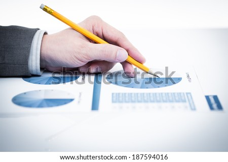 Businessman's hand showing financial report on table