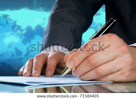 Businessman's hand with a pen.International business concept - stock photo