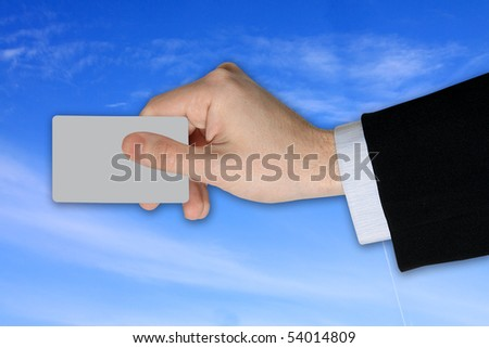 Businessman's Hand with blank credit Card on cloudy Sky