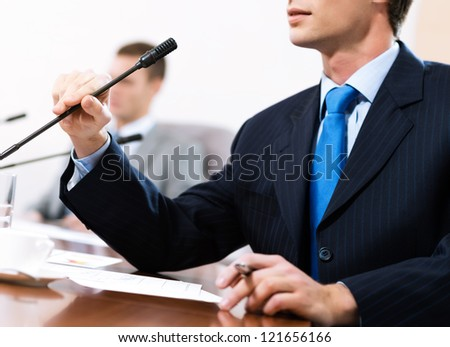 businessman, said into the microphone, in the background colleagues communicate with each other