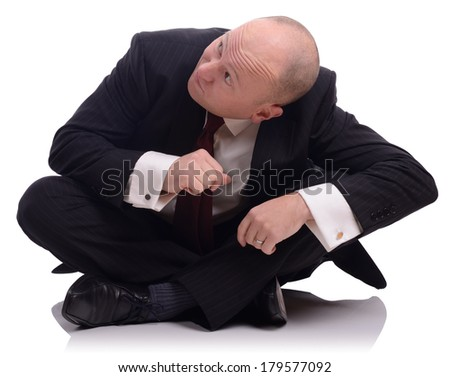 Businessman sat on the floor looking up and ducking down, isolated on a white background - stock photo