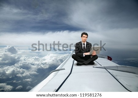 Businessman sat on the wing of an airplane - stock photo
