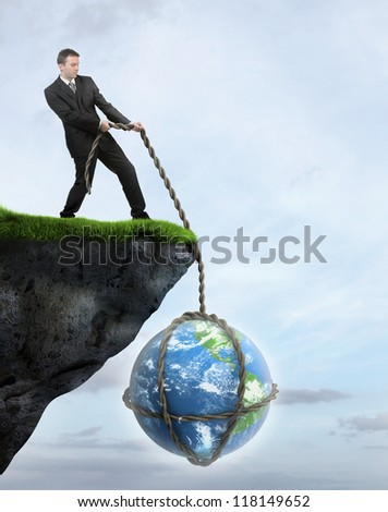 Businessman saving Earth from falling of the cliff. Elements of this image furnished by NASA - stock photo
