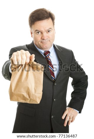 Businessman saving money by bringing his lunch to work in a brown bag.  He doesn't look happy.  Isolated. - stock photo