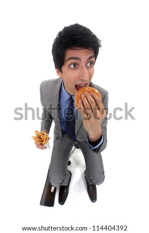 Businessman scoffing a burger and fries - stock photo