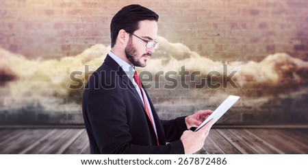 Businessman scrolling on his digital tablet against clouds in a room - stock photo
