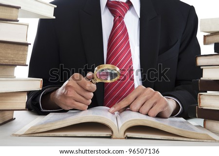 Businessman searching informations from the books by using magnifying - stock photo