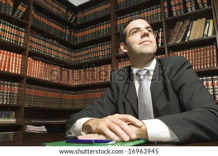 Businessman seated at desk in office looking peaceful. Horizontally framed photo. - stock photo