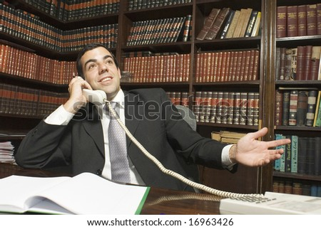 Businessman seated at desk talking on phone with bookshelves in the background. Horizontally framed photo. - stock photo