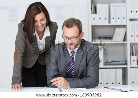 Businessman seated at his desk working with his secretary as the two look at a document together with his secretary, an attractive young woman, standing leaning over his shoulder - stock photo