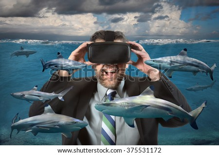 Businessman seeing sharks in the ocean using virtual reality glasses - stock photo