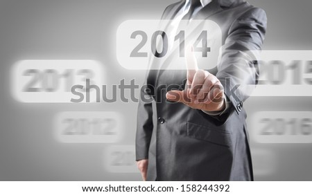 Businessman selects 2014 on touch screen - stock photo