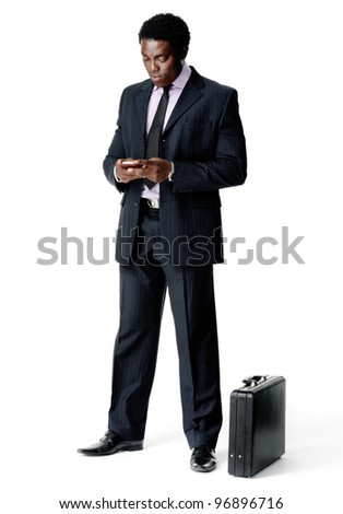 businessman sending a text message with his cell phone while his briefcase rests on the floor. isolated on white - stock photo