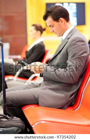 businessman sending or reading text messages at airport - stock photo