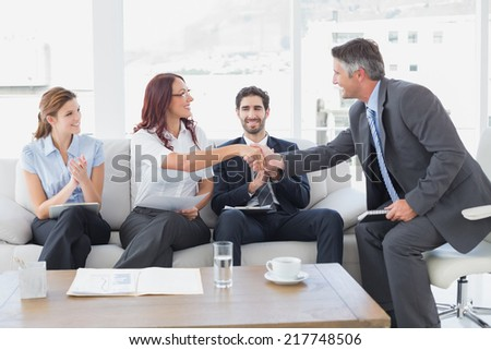Businessman shaking an employees hand in a meeting - stock photo