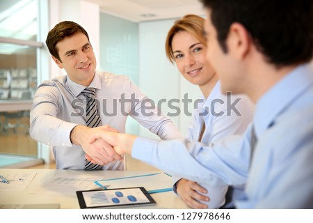 Businessman shaking hand to business partner - stock photo