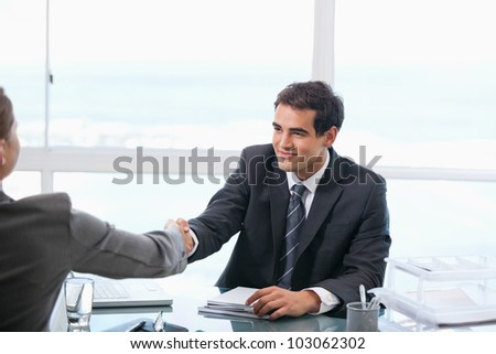 Businessman shaking hands with a client while sitting in an office - stock photo
