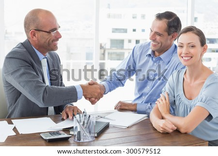 Businessman shaking hands with a co worker in an office - stock photo