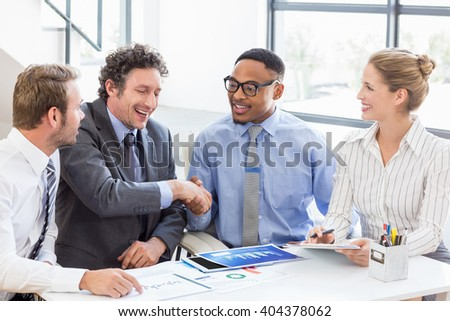 Businessman shaking hands with colleagues in meeting at office