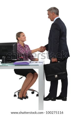 Businessman shaking hands with his new secretary - stock photo