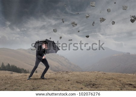 Businessman sheltering under an umbrella from rocks falling to the ground - stock photo