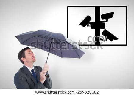 Businessman sheltering under black umbrella against cctv - stock photo
