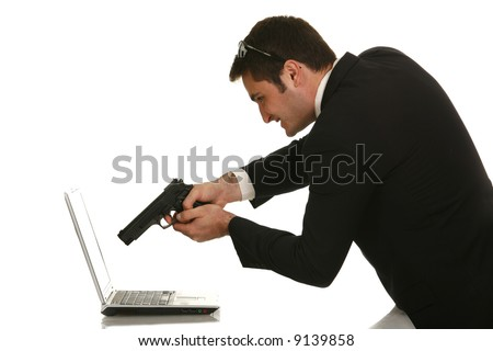 Businessman shooting his laptop computer with a handgun - stock photo