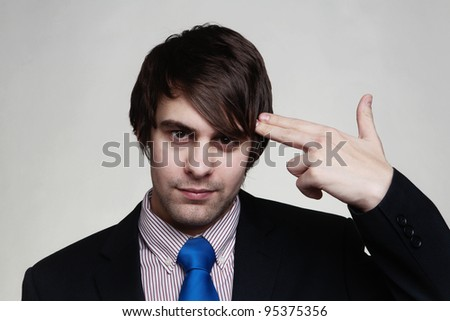 businessman shooting his own head with his fingers