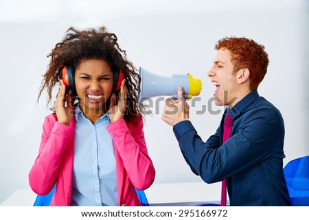 businessman shouting in megaphone to african executive with scared expression - stock photo