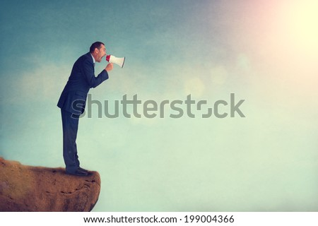 businessman shouting through a megaphone from a mountain edge - stock photo