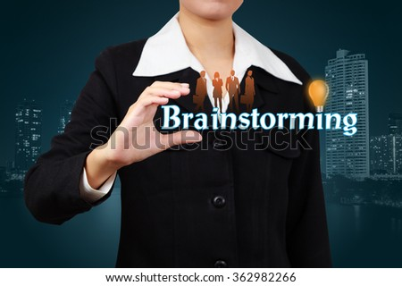 Businessman show Brainstorming word and brain with Light Bulb in palm. - stock photo