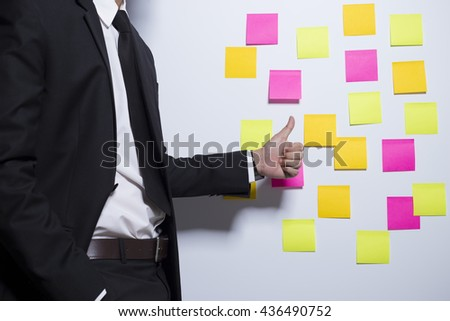 Businessman show thumb up on notepaper background
