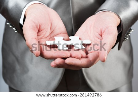 businessman show white jigsaw in hand, business strategy concept - stock photo
