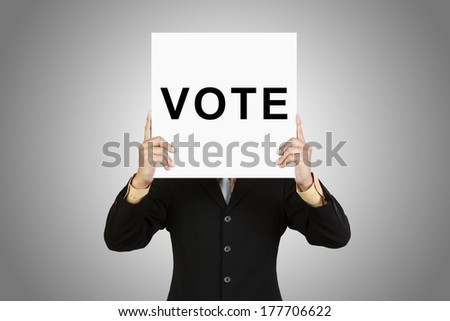 Businessman show wording VOTE on paper board on gray background