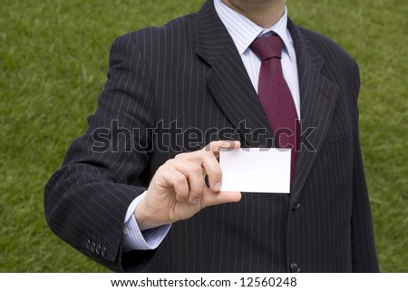 Businessman showing a blank card with copy space (selective and soft focus) - stock photo