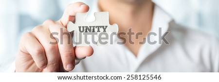 Businessman Showing a Conceptual White Jigsaw Puzzle Piece with Unity Text in Close up. - stock photo