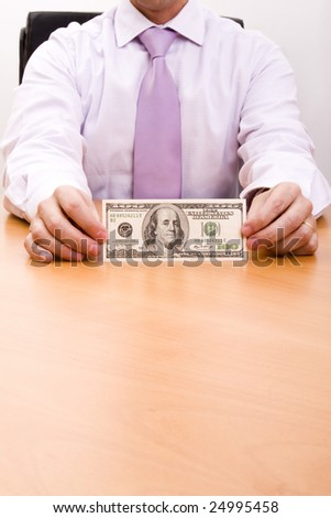 businessman showing a dollar bill at his office desk (selective focus)