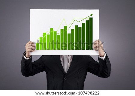 Businessman showing a green graphic of his business growth. shot in studio - stock photo