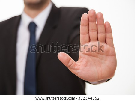 Businessman showing a sign of stop, white background - stock photo