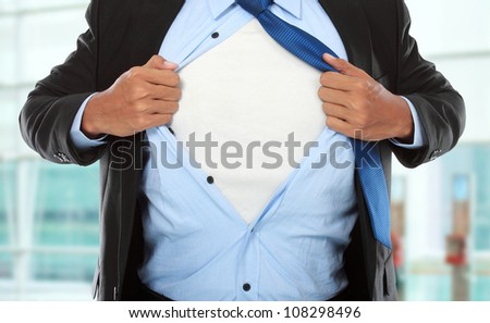 Businessman showing a superhero suit underneath his suit in the office - stock photo