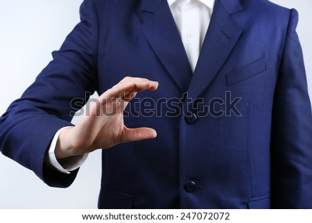 Businessman showing anything on grey background - stock photo