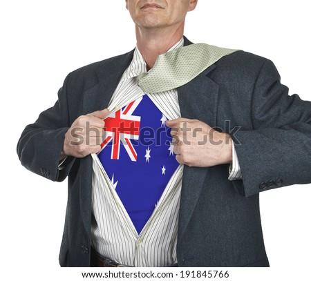 Businessman showing Australia flag superhero suit underneath his shirt standing against white background - stock photo