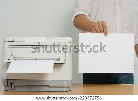 Businessman showing blank paper near color printer on table in office - stock photo