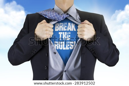 businessman showing Break the rules words underneath his shirt over blue sky - stock photo
