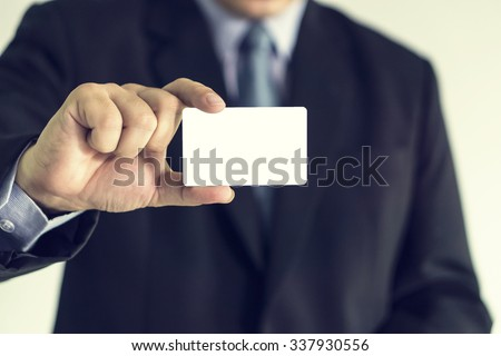 businessman showing business card ,Man's hand showing business card ,closeup shot,vintage color,selective focus. - stock photo