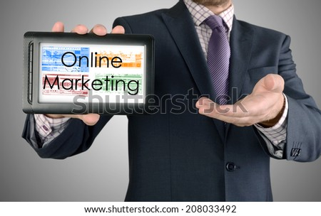 Businessman showing business concept on tablet - Online Marketing - stock photo