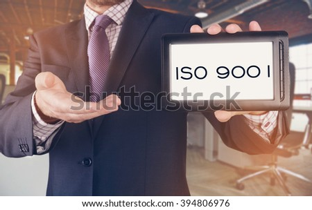 Businessman showing business concept on tablet standing in office - ISO 9001 - stock photo