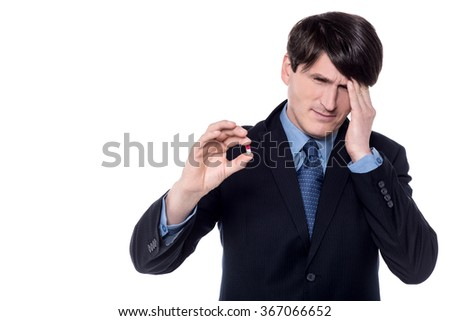 Businessman showing capsule with his hand on forehead