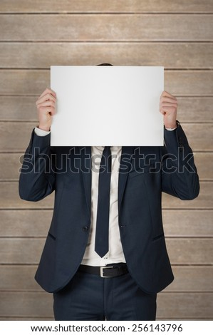 Businessman showing card to camera against wooden planks