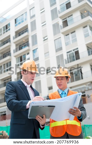 Businessman showing contractor the plan of the building - stock photo